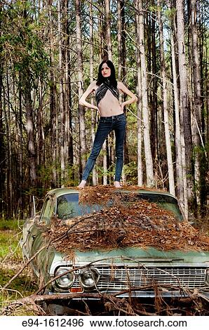Portrait of a 20 year old brunettte woman in jeans standing on an old car  in a forest setting