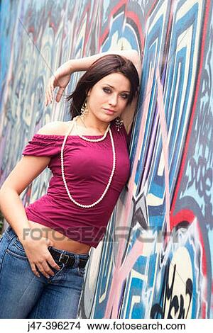 21 year old girl, standing against a wall graffitti, with a sultry look  into camera