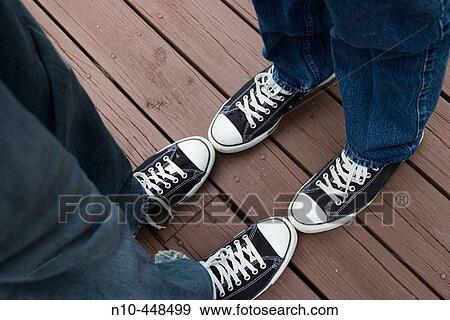 close up of two teen boys feet wearing identical sneakers