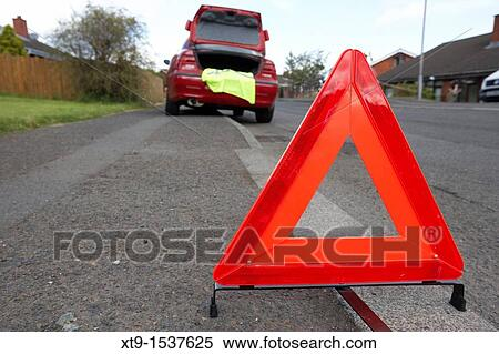 Stock Image - hazard warning triangle laid out on the side of the road in a