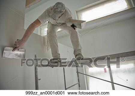 Stock photography of sheetrock worker at a public housing - Interior women s health fairbanks ak ...