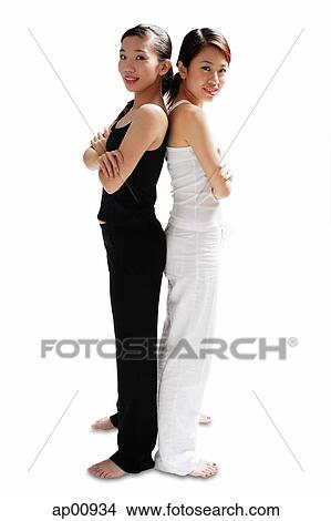 Stock Photo of Two women standing back to back, arms ...