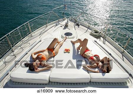 stock photograph of women sunbathing on boat deck high