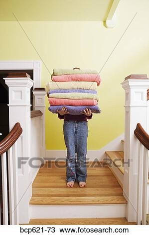 Stock Photo Of Child Carrying Tall Stack Of Towels On