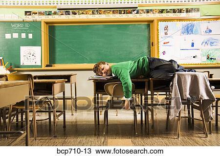 Boy Sleeping On Desks In Clroom