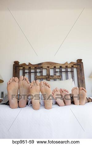 family lying on bed feet lined up