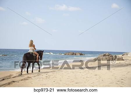 Stock Photography of Young woman riding horse on beach ...