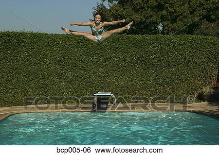 Stock Images Of Teenage Girl Does The Splits While Jumping Into A Swimming Pool Bcp005 06