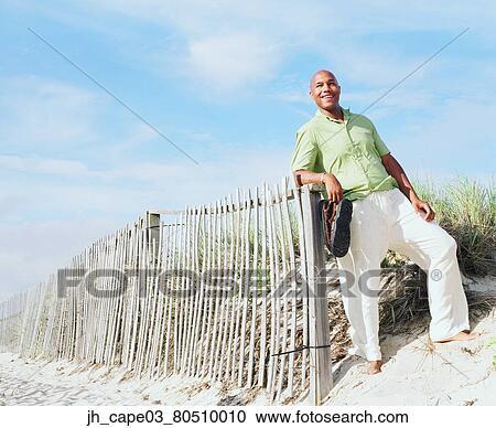 banques de photographies jeune homme debout s 39 appuyer a cl ture bois jh cape03 80510010. Black Bedroom Furniture Sets. Home Design Ideas