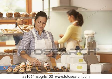 stock photo woman decorating cupcakes in bakery fotosearch search stock photography print