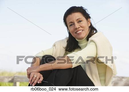 Stock Photo Of Middle Aged Woman Sitting Outdoors Rb06boo