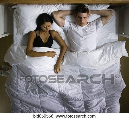 stock images of multi ethnic couple laying in bed bld050556 search stock photography poster. Black Bedroom Furniture Sets. Home Design Ideas
