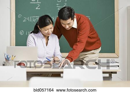 stock foto asiatische lehrer anschauen schreibarbeit. Black Bedroom Furniture Sets. Home Design Ideas