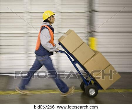 Stock images of asian warehouse worker pushing boxes on hand truck asian warehouse worker pushing boxes on hand truck sciox Choice Image