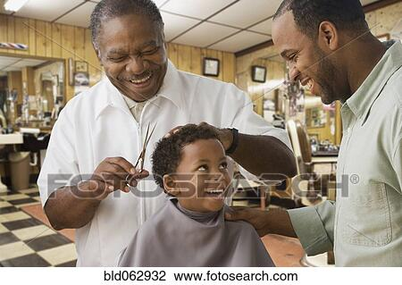 Stock Photo of African boy with father getting haircut at ...