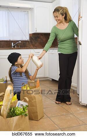 stock image of hispanic girl helping mother put away