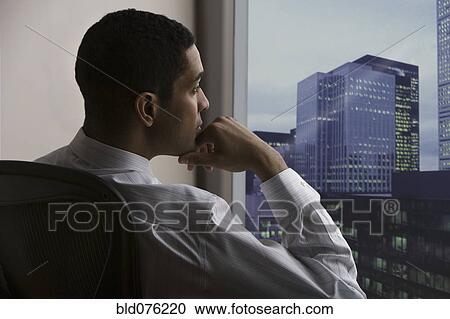 Stock Photography of Pensive mixed race businessman looking out ...