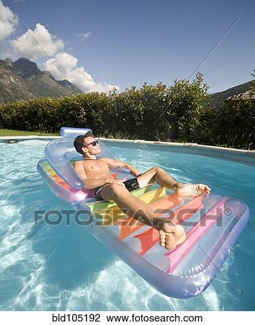 Man Floating In Swimming Pool On Inflatable Raft