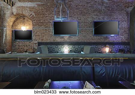 banque de photo trois tv crans sur mur brique dans restaurant derri re cuir si ge. Black Bedroom Furniture Sets. Home Design Ideas