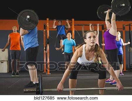 stock image of people lifting weights in gym bld127685