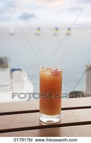 stock photo of full cocktail glass on table near marina