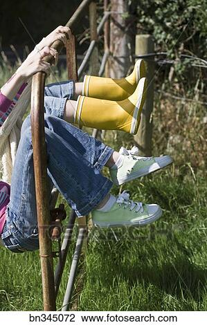 Stock Photo of Two children swinging on gate in fence ...