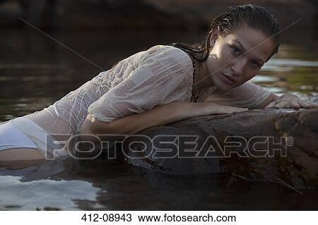 Stock photo of portrait of sensual woman laying on rock in for Laying river rock