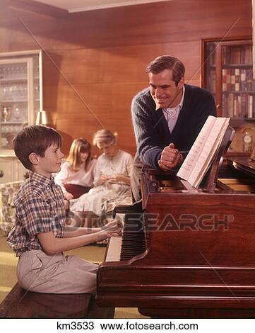 stock po 1970 1970s family living room boy son playing piano father listening mother