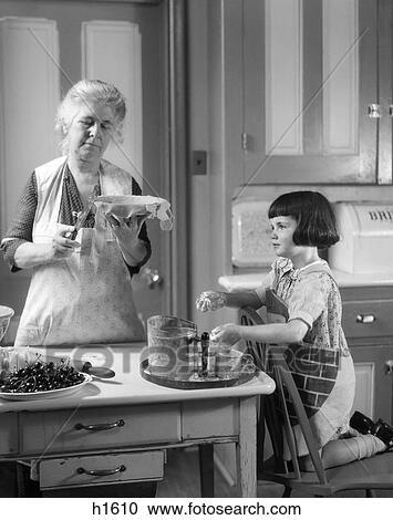 Archivio fotografico 1920s nonna e nipote in cucina - Nonne in cucina ...