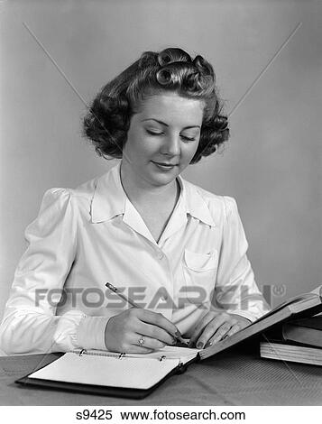 stock image of 1940 1940s young woman writing and studying