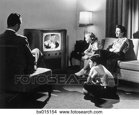 Living Room 1950s stock photo of 1950s couple in darkened living room watching tv
