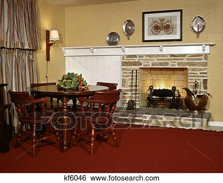 Stock Image   1960S 1970S Wood Burning Fireplace Stone Interior Country  Colonial Furniture Table Chairs Red
