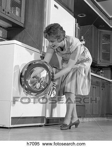 stock image of 1960s housewife in kitchen putting laundry