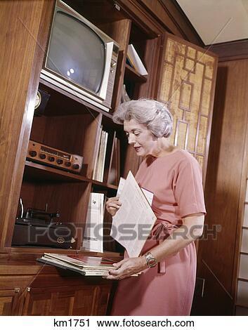 Stock fotografie 1960s middelbare leeftijd vrouw het selecteren melding gedenkboeken lang - Muurschildering volwassen kamer ...