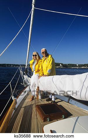 Pictures of senior couple wearing yellow jackets on bow of ...