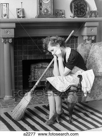 bild 1930s unzufriedene frau sitzen stuhl f hren hinunter vor kaminofen tragen schuerze. Black Bedroom Furniture Sets. Home Design Ideas
