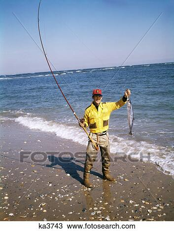 stock photo of 1970s man red cap hat yellow shirt waders