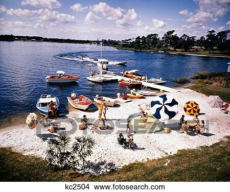 Stock photo of 1960s people on small sandy beach umbrellas for Cypress gardens mural