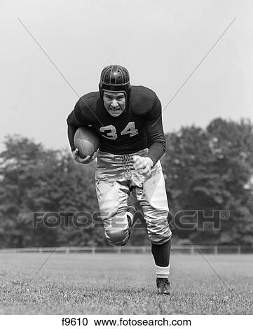 stock photography of 1940s football player holding