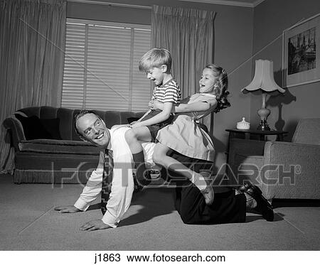 Stock Photo Of 1950s 1960s Dad Carrying Boy Amp Girl Piggyback On Living Room Floor J1863 Search