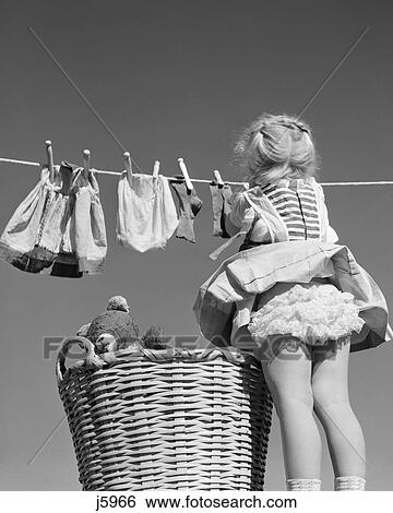 Images of 1950s back view of girl hanging laundry wind blowing skirt