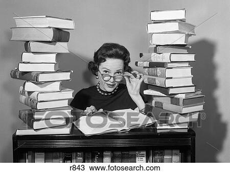 stock foto 1950s frau sitzen zwischen stapel von buecher ziehen unten brille schauen. Black Bedroom Furniture Sets. Home Design Ideas