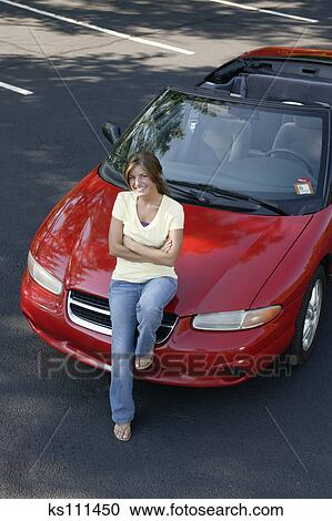 Types Of Car Insurance >> Stock Photography of Woman sitting on car hood, portrait, aerial angle ks111450 - Search Stock ...