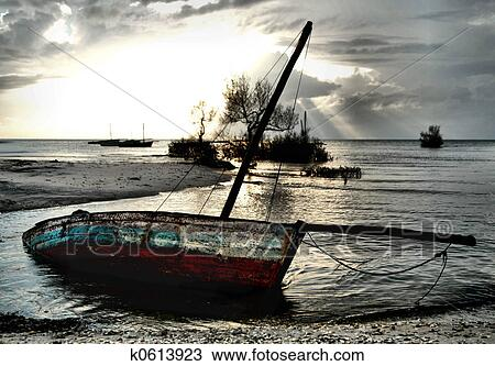 Stock Photo of Red and White Dhow Sailing boat stranded at ...