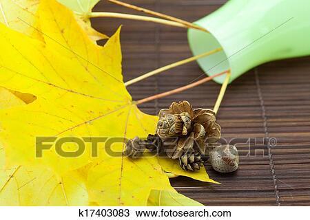 banque de photo jaune feuilles rable et bourgeons dans a vase sur a tapis bambou. Black Bedroom Furniture Sets. Home Design Ideas