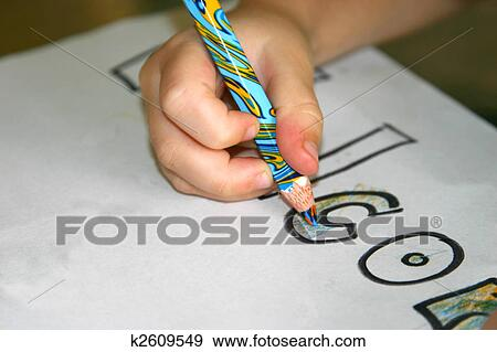 Stock Photograph of A closeup of a child colouring in with a ...
