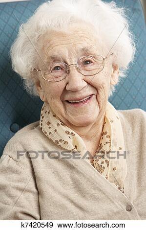 Banque de Photographies - femme aînée, délassant, dans chaise, chez soi. Fotosearch - Recherchez des Photos, des Images, des Photographies et des Images ClipsArts