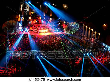 Stock image of dancing people at night outdoor concert for Concerts at the mural