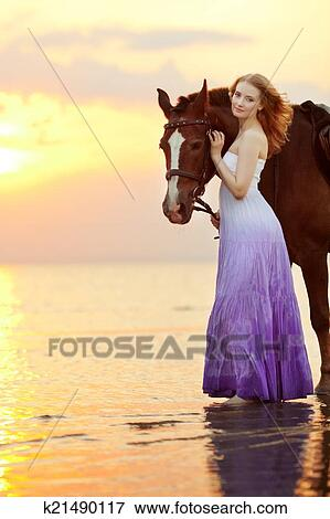 bild sch ne frau reiten a pferd an sonnenuntergang auf dass strand jung gir. Black Bedroom Furniture Sets. Home Design Ideas