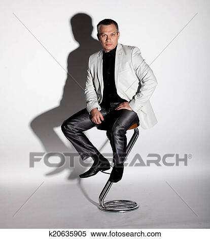 Stock Image Man In Suit Sitting On Bar Chair Against White Background Fotosearch